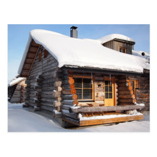 Snow-covered log cabin in Lapland postcard