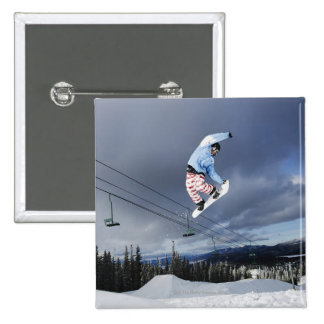 Snowboarder jumping in mid-air doing a backside 15 cm square badge