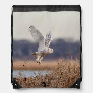 Snowy owl taking off drawstring bag