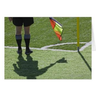 Soccer referee holding flag. card