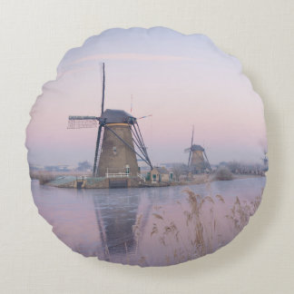 Soft sunrise light in winter over windmills round cushion