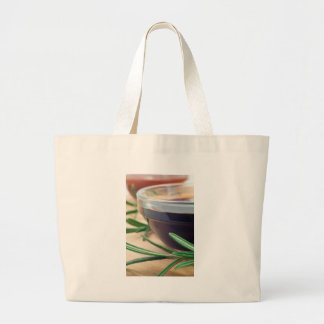 Soy sauce in a glass and a sprig of rosemary large tote bag