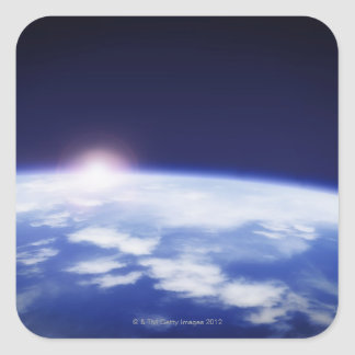 Space with rising sun above planet earth square sticker