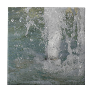 Splashes of fountain water in a sunny day tile