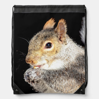 Squirrel eating a nut drawstring bag