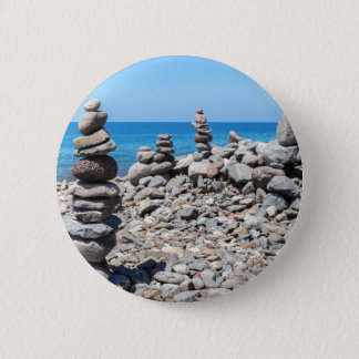 Stacked beach stones at blue sea 6 cm round badge
