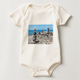 Stacked beach stones at blue sea baby bodysuit