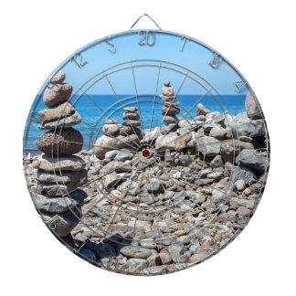 Stacked beach stones at blue sea dartboard
