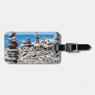 Stacked beach stones at blue sea luggage tag