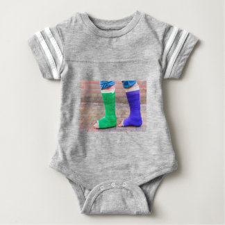 Standing child with two colorful gypsum legs baby bodysuit