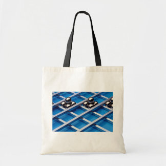 Steel balls and rods on blue acrylic tote bags