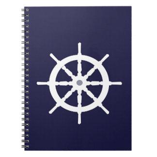 Steering wheel on navy blue background. notebooks