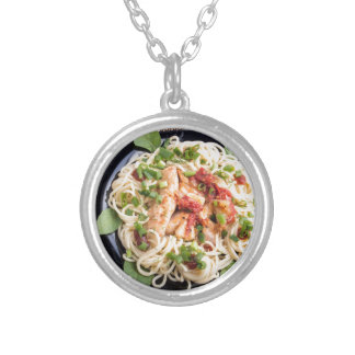 Stewed chicken with tomato sauce on a plate silver plated necklace