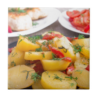 Stewed potatoes with bell pepper closeup small square tile