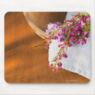 Still life with purple flowers, towel and wooden mouse pad