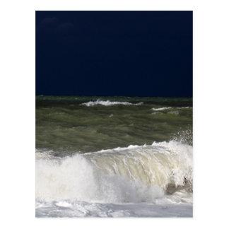 Stormy sea with waves und a dark blue sky. postcard