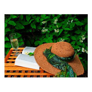Straw hat, book and white wine in a summer garden postcard