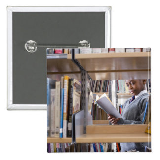 Student in school uniform looks at a book in a 15 cm square badge