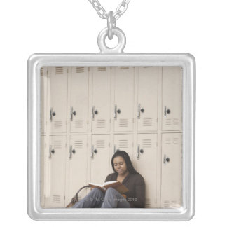 Student leaning on school lockers studying silver plated necklace
