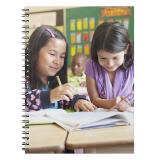 Students working together in classroom spiral note book