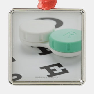 Studio shot of contact lens case on eye chart metal ornament