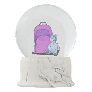 Stuffed Unicorn sits by a purple school Backpack Snow Globe