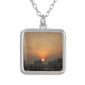 Sunrise at a lake with flying birds. silver plated necklace