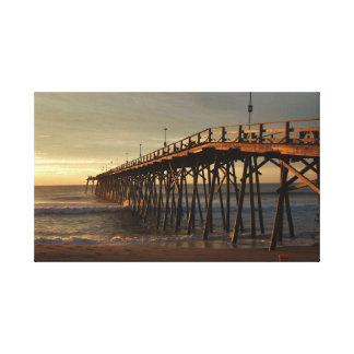Sunrise at the beach by the pier canvas print