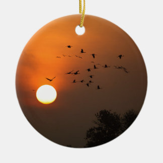 Sunrise with flocks of flying cranes ceramic ornament
