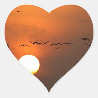 Sunrise with flocks of flying cranes heart sticker