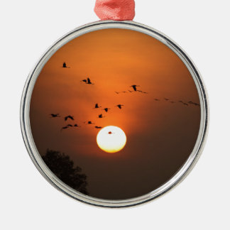 Sunrise with flocks of flying cranes metal ornament