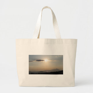 Sunset over mountains large tote bag
