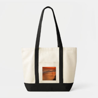 Sunset reflections off clouds and ocean shore impulse tote bag