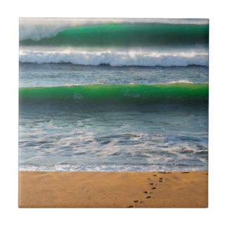 Surfer footprints on sand beach and green waves tile
