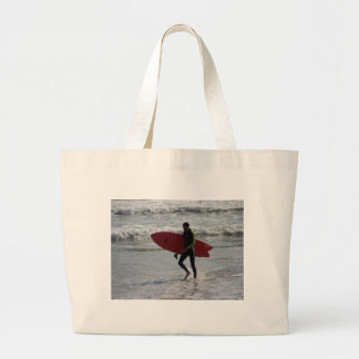 Surfer with surf board with waves large tote bag