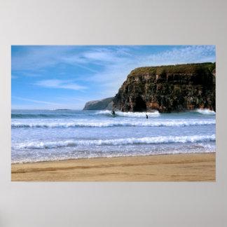 surfers surfing near Ballybunion cliffs Poster