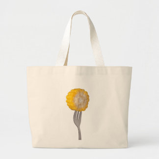 Sweet corn held by a fork bags