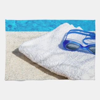 Swimming goggles and towel near swimming pool