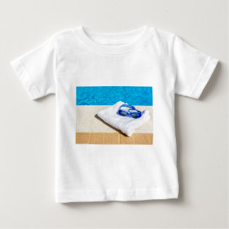 Swimming goggles and towel near swimming pool baby T-Shirt