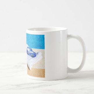 Swimming goggles and towel near swimming pool coffee mug