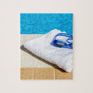 Swimming goggles and towel near swimming pool jigsaw puzzle