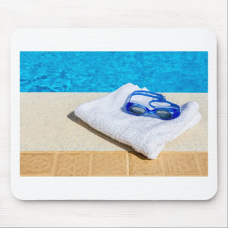 Swimming goggles and towel near swimming pool mouse pad