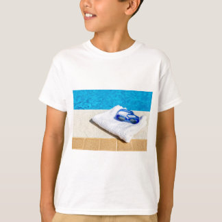 Swimming goggles and towel near swimming pool T-Shirt