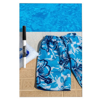 Swimming trunks goggles and towel at pool dry erase board