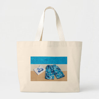 Swimming trunks goggles and towel at pool large tote bag