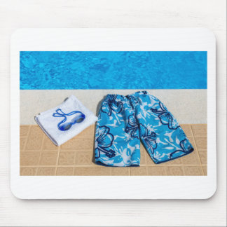 Swimming trunks goggles and towel at pool mouse pad