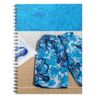 Swimming trunks goggles and towel at pool notebooks