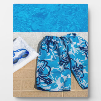 Swimming trunks goggles and towel at pool plaque