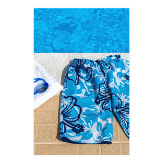 Swimming trunks goggles and towel at pool stationery