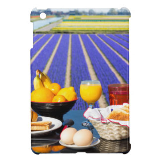 Table with food and drink near flowers field iPad mini case